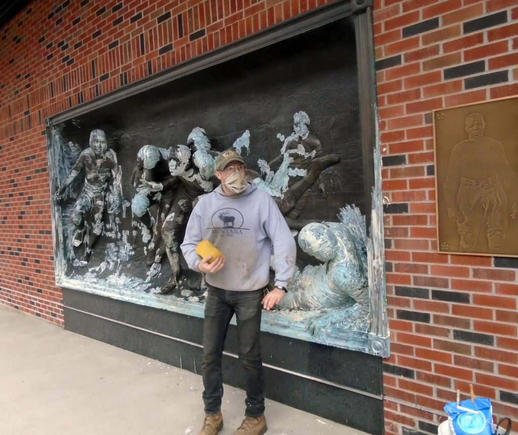 Drew posing as a football player, anti-corrosion poultice working away in background at Kinnick Stadium, University of Iowa, Max-Cast
